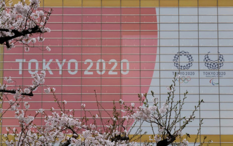 The logo of the Tokyo 2020 Olympic Games and Paralympic Games is displayed behind cherry blossoms in Tokyo on 30 March 2020. Picture: AFP