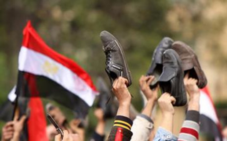 Egyptian anti-government protesters wave their shoes outside the state television building in Cairo on 11 February 2011. Picture: AFP