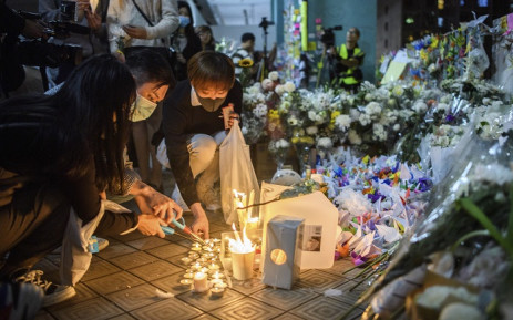 "Mourners pay their respects next to flowers and a banner which reads ""From all of us - God bless Chow Tsz-Lok"" at the site where student Alex Chow, 22, fell during a recent protest in the Tseung Kwan O area on the Kowloon side of Hong Kong on 8 November 2019. Picture: AFP"