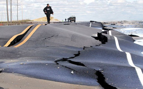 A sheriff walks on a New Jersey road damaged by Superstorm Sandy on 30 October 2012. Picture: Twitter