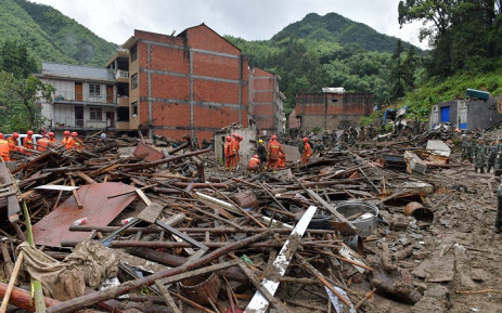 FILE: Rescuers look for survivors in the rubble of damaged buildings after a landslide caused by torrential rain from Typhoon Lekima, at Yongjia, in Wenzhou, in China's eastern Zhejiang province on 10 August 2019. Picture: AFP