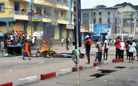 FILE: People stand beside burning objects in the middle of the street on 19 January, 2015 in Kinshasa. Picture: AFP.
