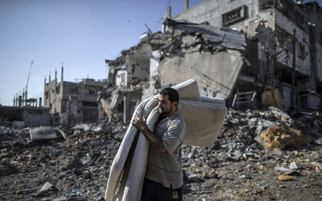 A Palestinian carries mattresses he found in the rubble of destroyed buildings on 27 July, 2014 in the Shejaiya residential district of Gaza City as families returned to find their homes ground into rubble by relentless Israeli tank fire and air strikes. Picture: AFP.