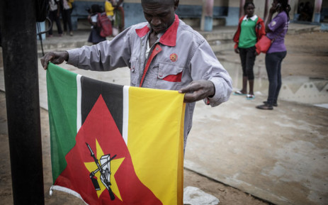 FILE: A school janitor folds the Mozambican national flag at sunset inside a Public School on 4 July, 2018 in Nacala, Mozambique. Picture: AFP