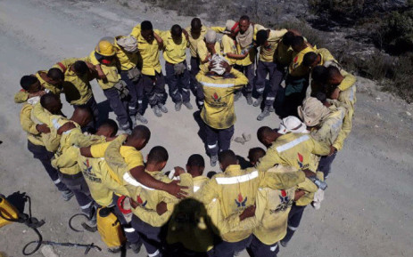 Working on Fire members pray after hearing about the passing of Nico Heyns, who was killed when his helicopter crashed while fighting a fire in  Vermaaklikheid on 23 October 2018. Picture: @wo_fire/Twitter.