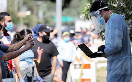 A testing associate dressed in personal protective equipment helps people waiting in line to check in at a COVID-19 testing centre at Lincoln Park amid the coronavirus pandemic on 7 July 2020 in Los Angeles, California. Picture: AFP.
