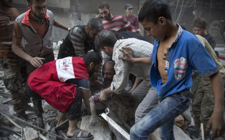Syrians surround a man as he cries over the body of his child after she was pulled out from the rubble of a building following government forces air strikes in the rebel held neighbourhood of Al-Shaar in Aleppo on 27 September 2016. Picture: AFP.