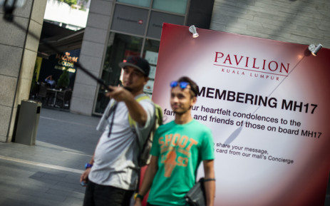 Visitors take selfies in front of prayers and well-wishes for passengers onboard Malaysia Airlines flight MH17 that crashed in eastern Ukraine, at a shopping mall in Kuala Lumpur on July 19, 2014. Picture: AFP.