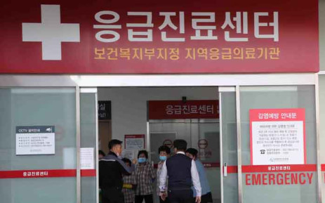 In this picture taken on 21 January 2020, cleaning workers in uniforms wear face masks next to a notice on preventing infection at a hospital, where a Chinese woman who was confirmed to have the new coronavirus strain is isolated, in Incheon. Picture: AFP