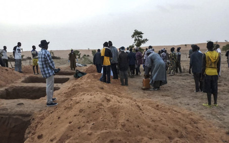 Officials and residents stand near freshly dug graves on 11 June 2019 in the Dogon village of Sobane-Kou, near Sangha, after an attack that killed over 100 ethnic Dogon on 9 June 2019 evening. Picture: AFP
