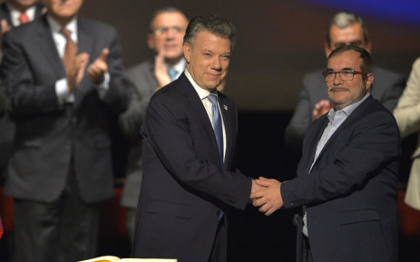 Colombian President Juan Manuel Santos (L) and the head of the FARC guerrilla Timoleon Jimenez shake hands during the second signing of the historic peace agreement. Picture: AFP