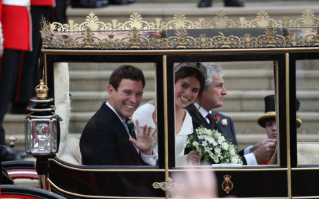 Britain's Princess Eugenie of York (R) and her husband Jack Brooksbank (L) get into the Scottish State Coach at the start of their carriage procession following their wedding at St George's Chapel, Windsor Castle in Windsor, on 12 October 2018. Picture: AFP