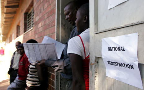 FILE: A voter registration official inspects identity particulars at Lotshe Primary School in Bulawayo, Zimbabwe on 7 May 2013 during the mobile voter registration exercise. Picture: AFP