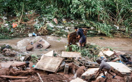 FILE: A man tries to salvage some of his furniture at an informal settlement of BottleBrush, south of Durban, after torrential rains and flash floods destroyed his home on 23 April 2019. Picture: AFP