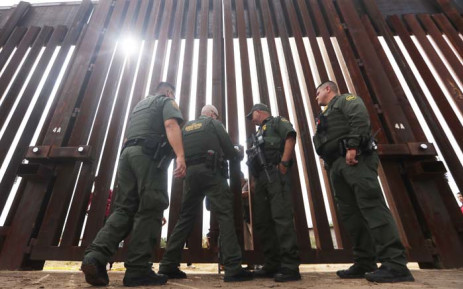 US border patrol agents lock the border wall gate at the conclusion of the Hugs Not Walls event on the US-Mexico border on 13 October 2018 in Sunland Park, New Mexico. Picture: AFP