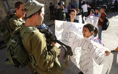 Palestinian children demonstrate near an Israeli check point in the centre of the West Bank city of Hebron after they couldn't pass the checkpoint to get to school as it was closed off by Israeli security forces on 26 August, 2014. Picture: AFP.