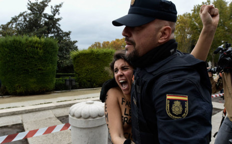 Police officers subdue a member of feminist movement Femen as she protests against a far right demonstration marking the anniversary of the death of Spanish dictator Francisco Franco in Madrid on 18 November 2018. Picture: AFP