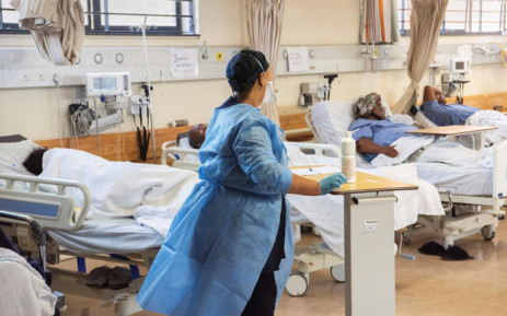 FILE: A hospital worker walks amongst patients in the COVID-19 ward at Khayelitsha Hospital, about 35km from the centre of Cape Town, on 29 December 2020. The patents in this ward are not critically serious, but do require oxygen and to lie down. Picture: Rodger Bosch/AFP.