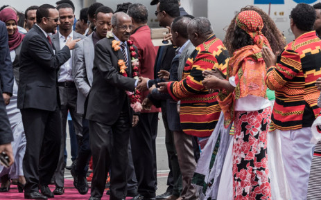 Eritrea's Foreign Minister Osman Saleh Mohammed (C) walks with Ethiopia's Prime Minister Abiy Ahmed (L) shaking hands with dignitaries as an Eritrean delegation for peace talks with Ethiopia arrives at the international airport in Addis Ababa on 26 June 2018. Picture: AFP