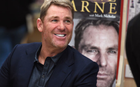 """FILE: Australian cricketing great Shane Warne chats with a customer during a book signing event for his new autobiography titled """"No Spin"""", in Melbourne on 19 October 2018. Picture: AFP"""