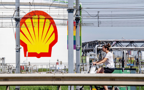 FILE: A woman rides her bicycle past the Shell Pernis site in Rotterdam on 30 July 2020. Picture: Robin Utrecht/AFP