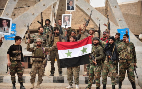 FILE: A handout picture released by the official Syrian Arab News Agency (SANA) on 21 November 2017 shows members of the pro-Syrian government forces posing with portraits of Syrian President Bashar al-Assad and his late father Hafez al-Assad. Picture: AFP.