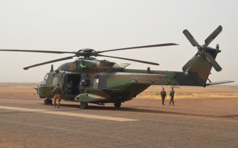 A photo taken on 25 July, 2017 shows a German helicopter crew near their NH90 Caiman transport helicopter on the ground at Gao airport in Mali. Picture: AFP.