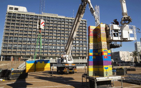 Workers and volunteers help assemble bricks during the construction of a Lego tower in Tel Aviv's Rabin Square on 26 December, 2017, as the city attempts to break Guinness world record of the highest such structure. Picture: AFP