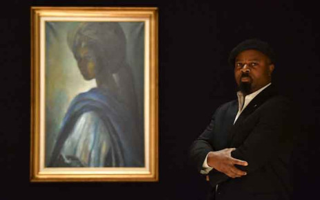 Nigerian author Ben Okri poses with a work of art by Nigerian painter and sculptor Ben Enwonwu entitled 'Tutu' expected to realise $278000-$417,000 at auction in Bonhams auction house London on 7 February 2018. Picture: AFP.