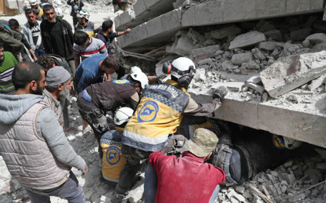 """FILE: Members of the Syrian Civil Defence, also known as the """"White Helmets"""", search the rubble of a collapsed building following an explosion in the town of Jisr al-Shughur, in the west of the mostly rebel-held Syrian province of Idlib, on 24 April 2019. Picture: AFP"""