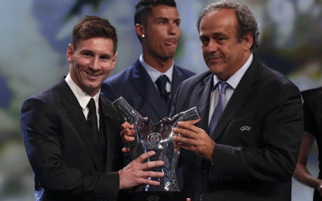 FC Barcelone Argentinian striker Lionel Messi (L) receives from UEFA president Michel Platini (R) the trophy of Best Men's player in Europe next to runner-up Portugal's Cristiano Ronaldo at the end of the UEFA Champions League Group stage draw ceremony, on August 27, 2015 in Monaco. Picture: AFP.