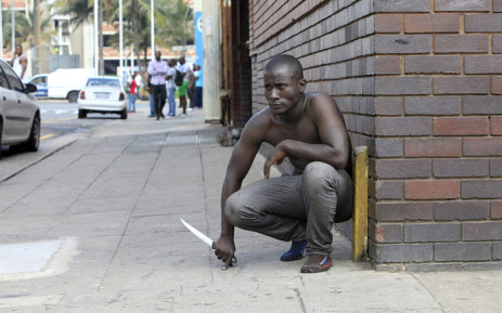 FILE: A foreign national holds a knife following clashes between a group of locals and police in Durban on 14 April 2015. Picture: AFP.