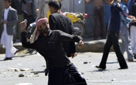 Yemeni anti-government protesters throw stones towards regime loyalists during clashes in central Sanaa. Picture: AFP