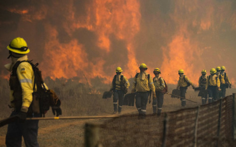 Firefighters leave an area where the flames become too aggressive, as a forest fire burns out of control on the foothills of Table Mountain, above the University of Cape Town, in Cape Town, on 18 April 2021. Picture: Rodger Bosch/AFP