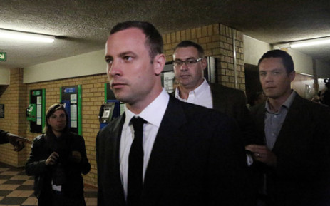 Oscar Pistorius is escorted into the High Court in Pretoria on the first day of his trial for murder. Picture: Sebabatso Mosamo/EWN.