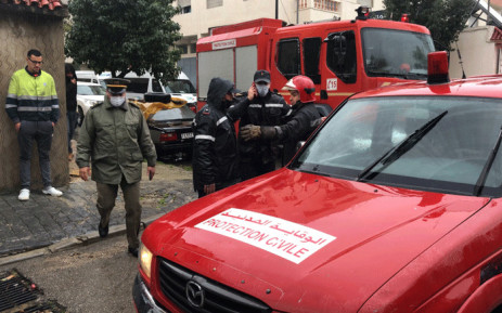 Emergency services gather at the site of illegal underground textile workshop that flooded after heavy rain fall in Morocco's city of Tangiers on February 8, 2021.  Picture: AFP.