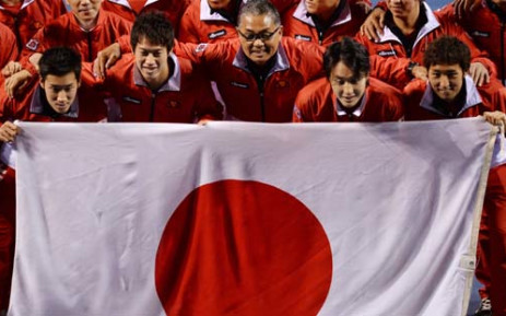 JAPAN, Tokyo : Japan team captain Minoru Ueda (C) and players (from L) Yuichi Sugita, Kei Nishikori, Go Soeda and Yasutaka Uchiyama, pose behind the national flag with other team officers to celebrate their victory over Canada in Davis Cup tennis 2014 World Group first round in Tokyo on February 2, 2014. Japan beat Canada 4-1. Picture: AFP.