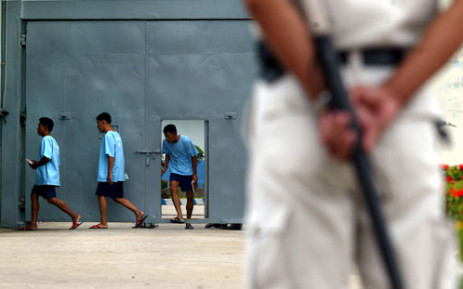 A prison police stands guard with a baton as he watches inmates enter a compound at Bangkok's Klong Prem Prison. Picture: AFP