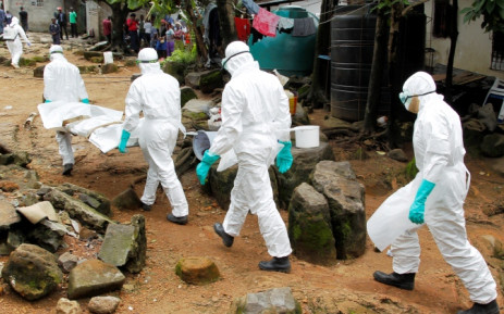 Liberian nurses carry the body of a suspected victim of Ebola at the Sonuwein community in Monrovia, Liberia, 3 October 2014. Picture: EPA/Ahmed Jallanzo.