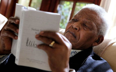 Former South African President Nelson Mandela is pictured reading a book by Debbie Yazbek/Nelson Mandela Foundation/SAPA