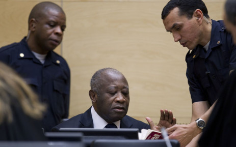 Former President of Côte d'Ivoire Laurent Gbagbo (centre), surrounded by security guards at the International Criminal Court. Picture: United Nations Photo.