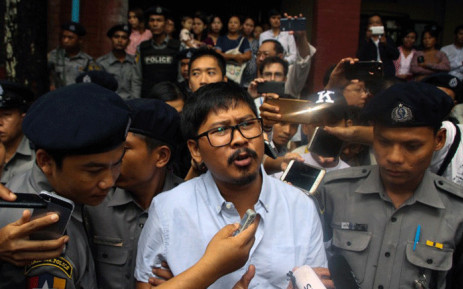 Detained Myanmar journalist Wa Lone (C) speaks to reporters as he is escorted by police from a courthouse following his ongoing pre-trial hearing in Yangon on 9 July, 2018. Picture: AFP.