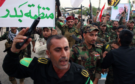 Members of Shiite factions hold banners and flags during a demonstration to protest against the Saudi-led Arab coalition which is carrying out air strikes on Huthi militia targets across Yemen on 31 March, 2015. Picture: AFP.