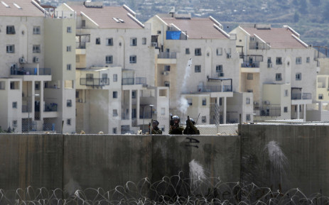 FILE: Members of the Israeli security forces fire a tear gas canister from the top of Isreals controversial separation barrier during clashes with Palestinians demonstrators in the village of Bilin, near the West Bank city of Ramallah following a march in support of the resistance in the Gaza Strip. Picture: AFP.