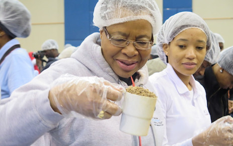 Graca Machel helps to package 1-million meals at the Stop Hunger Now Nelson Mandela 67-minute initiative. Picture: Louise McAuliffe