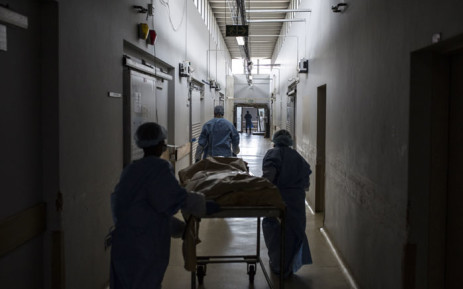 FILE: Forensic scientist Craig Keyes (C) and two forensic students from Wits University take an unidentified body for examination on 3 March 2019 in Johannesburg. Picture: AFP.