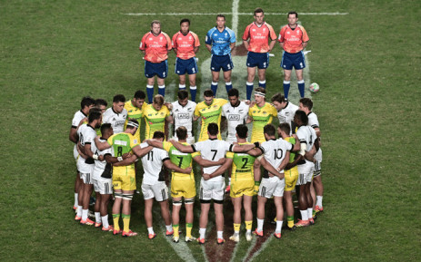 New Zealand's (white) and Australia's (yellow) players take part in a group huddle and a moment of silence before their match at the annual Rugby Sevens tournament in Hong Kong on 5 April 2019, in tribute to the 50 victims who lost their lives in the twin mosque massacre in Christchurch on 15 March. Picture: AFP.
