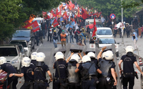 Protesters face Turkish riot police using tear gas in Ankara on 14 May, 2014, during a demonstration gathering hundreds after more than 200 people were killed in an explosion at a mine. Picture: AFP.