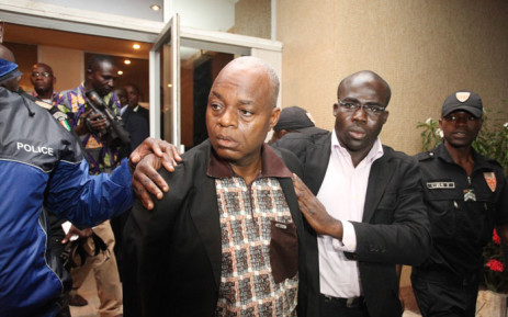 In this handout picture received from the Ivorian Government Press Moise Lida Kouassi (L) a key ally of Ivory Coast's ex-President Laurent Gbagbo is led away following his arrival in Abidjan on 6 June 2012. Picture: AFP
