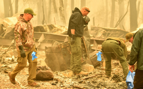 Yuba and Butte County Sheriff officers react as they discover a body at a burned out residence after the camp fire tore through the area in Paradise, California on 10 November 2018. Picture: AFP.